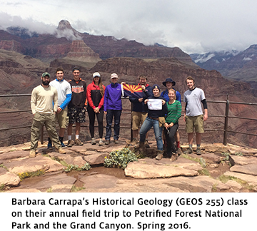 A group of undergraduate students and their professor hold UA Geosciences flags at a Grand Canyon lookout.