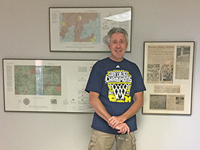 Steve Catlin poses with a wall display of lunar maps and news clippings