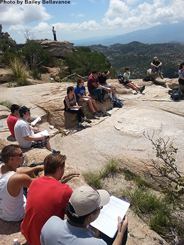 A group of students sit on Mt. Lemmon listening to a professor