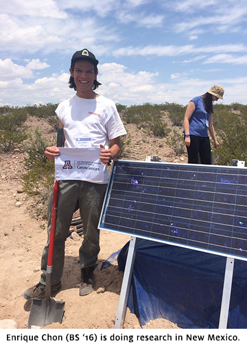 Enrique Chon holding Geosciences flag in field in New Mexico
