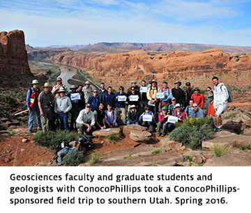 Faculty, graduate students, and other geologists holding UA Geosciences flags in front of a canyon in southern Utah.