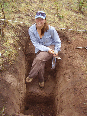 A smiling scientist sits in a dirt trench holding a trowel