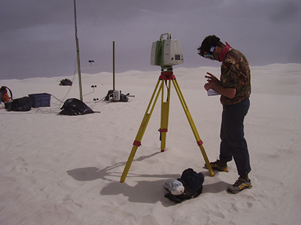 A scientist works with equipment in white sand