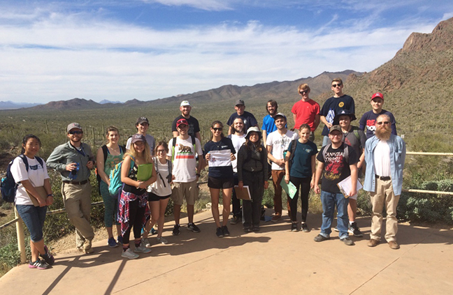 A group of students and a professor pose for a photo at Gates Pass.