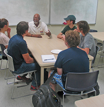 A group of students sit around a table with a mentor at a career workshop