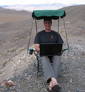 Keith Meldahl sits in a camping chair with his laptop in the Cadelaria Hills