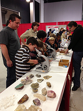 Children and their parents look through microscopes at tables covered with rocks