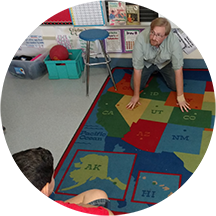A geosciences researcher crouches on a large US map rug in a classroom as a student looks on.