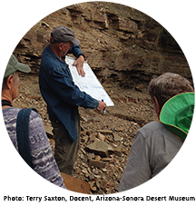 Professor George Davis holds a diagram and pen and talks to a group of docents in front of a rock face.
