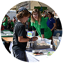 An undergraduate student talks to a child at the Geosciences table of the Tucson Festival of Books