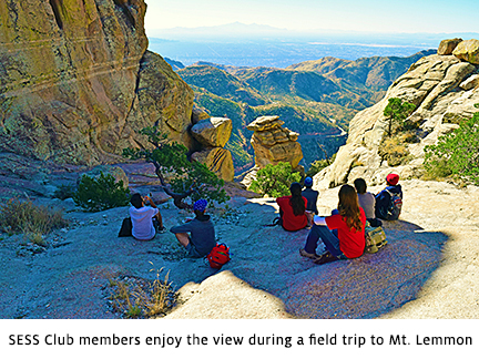 Students sit looking over a scenic overlook in the shadow of a cliff on Mount Lemmon.