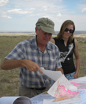 A professor and a student look at maps in the field