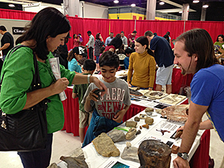 A woman and her son talk with a UA Geosciences graduate student at the Geosciences table of the Tucson Gem and Mineral Show