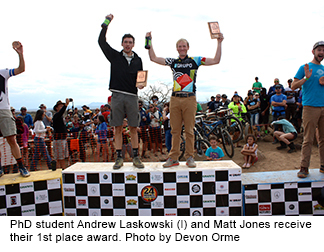 Two men stand on the winners' podium receiving their award.