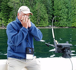George Davis playing harmonica on a motor boat on a lake
