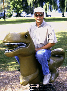 Karl Flessa sitting on a dinosaur playground piece