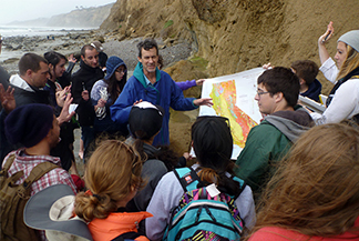 Students and faculty member reading an map on the coast