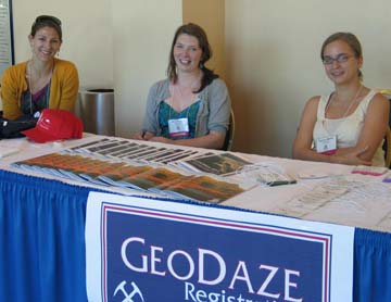 Graduate students sit at the GeoDaze registration table to welcome guests