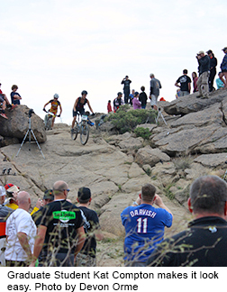 Woman on mountain bike rides down a rock face as others watch.
