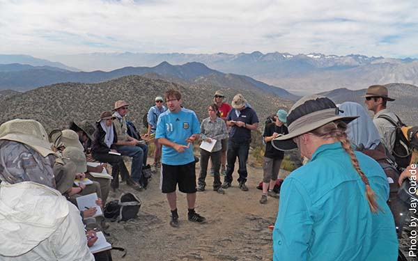 A faculty lectures to students on a fieldtrip overlooking mountains