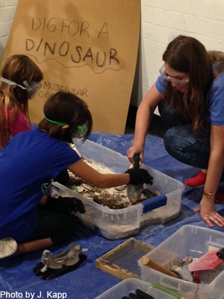 "A Geosciences undergraduate students does a hands-on ""dinosaur did"" with children visiting the Tucson Gem and Mineral Show."