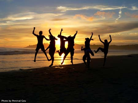Students on beach leaping in air in front of sunset
