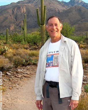 Marc Sbar on a hike in Tucson with mountains and saguaros in background.