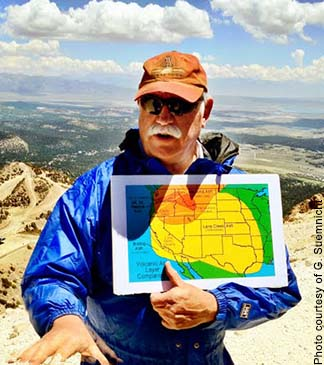 Gene Suemnicht holding a map and speaking at the summit of Mammoth Mountain in Long Valley caldera